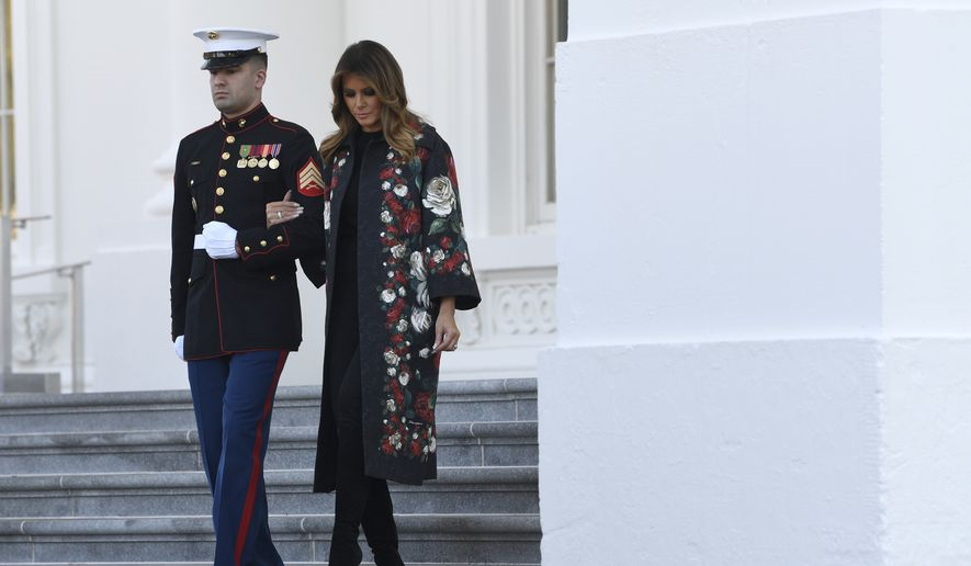 First lady Melania Trump is escorted as she walks out to take delivery of the 2019 White House Christmas tree as it arrives at the White House in Washington, Monday, Nov. 25, 2019. The Douglas fir is approximately 23 feet tall and was grown by Larry and Joanne Snyder at Mahantongo Valley Farms in Pennsylvania. Since 1966, the National Christmas Tree Association has held a contest that awards its winner with the honor of presenting their tree to the first family and will serve as a centerpiece for Christmas decorations in the Blue Room of the White House. (AP Photo/Susan Walsh)