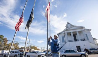 The flags are put at half staff before the first court appearance for William Johnson, suspect in fatal shooting of Lowndes County Sheriff John Williams, at the Lowndes County Courthouse in Hayneville, Ala., on Monday, November 25, 2019. (Mickey Welsh/Montgomery Advertiser via AP)