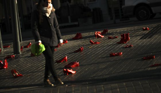 A woman walks among dozens of red painted shoes placed on the ground as a part of an installation against violence against women in Brussels, Monday, Nov. 25, 2019. (AP Photo/Francisco Seco)