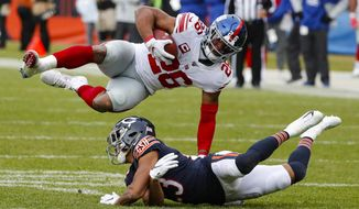 New York Giants running back Saquon Barkley (26) flips over Chicago Bears cornerback Kyle Fuller (23) during the second half of an NFL football game in Chicago, Sunday, Nov. 24, 2019. (AP Photo/Charles Rex Arbogast)