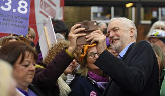 Britain's Labour Party leader Jeremy Corbyn poses for pictures with supporters as he visits the Renishaw Miners Welfare, in Sheffield, England, Monday Nov. 25, 2019, ahead of the general election on Dec. 12. Labour, under left-wing leader Jeremy Corbyn, has set out plans for a radical expansion of public spending and state ownership if it wins the election. (Joe Giddens/PA via AP)