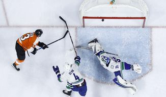 Philadelphia Flyers' Kevin Hayes (13) cannot get a shot past Vancouver Canucks' Jordie Benn (4) and Thatcher Demko (35) during the second period of an NHL hockey game, Monday, Nov. 25, 2019, in Philadelphia. (AP Photo/Matt Slocum)
