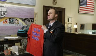 """Tim Eyman, a career anti-tax initiative promoter, holds up a t-shirt that reads """"Let the Voters Decide,"""" as he talks to reporters, Monday, Nov. 25, 2019, at the Capitol in Olympia, Wash. Eyman was in Olympia to officially announce his entry into the 2020 governor's race as an independent. (AP Photo/Ted S. Warren)"""