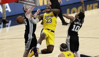 Los Angeles Lakers forward LeBron James (23) is fouled as he drives to the basket between San Antonio Spurs guard DeMar DeRozan (10) and center Jakob Poeltl (25) during the second half of an NBA basketball game, in San Antonio, Monday, Nov. 25, 2019. (AP Photo/Eric Gay)