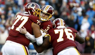 Washington Redskins kicker Dustin Hopkins, center, is mobbed by offensive guard Ereck Flowers (77) and offensive tackle Morgan Moses (76) after kicking the eventual game-winning field goal in the final seconds of the second half of an NFL football game against the Detroit Lions, Sunday, Nov. 24, 2019, in Landover, Md. The Redskins won 19-16. (AP Photo/Patrick Semansky)