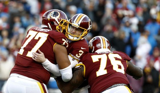 Washington Redskins kicker Dustin Hopkins, center, is mobbed by offensive guard Ereck Flowers (77) and offensive tackle Morgan Moses (76) after kicking the eventual game-winning field goal in the final seconds of the second half of an NFL football game against the Detroit Lions, Sunday, Nov. 24, 2019, in Landover, Md. The Redskins won 19-16. (AP Photo/Patrick Semansky) ** FILE **