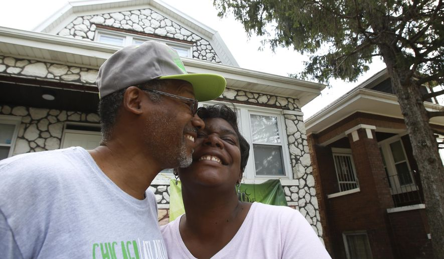 """Hasan and Mary Smith stand cheek to cheek outside their newly rehabbed home in the Chicago Lawn neighborhood of Chicago on Sept. 11, 2019. The home is one of dozens of """"reclaimed"""" houses and apartment buildings that became vacant during the mortgage crisis that began in 2008. Hasan and Mary met five years ago at a grocery store. Drawn to her talkative, upbeat nature, Smith told a friend, """"That's gonna be my girl."""" (AP Photo/Martha Irvine)"""
