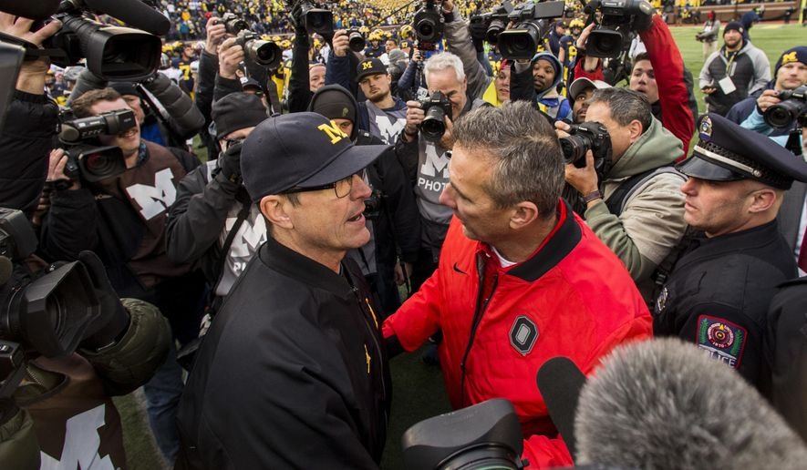 FILE - In this Nov. 25, 2017, file photo, Michigan head coach Jim Harbaugh, center left, shakes hands with Ohio State head coach Urban Meyer, center right, after Ohio State defeated Michigan 31-20 in an NCAA college football game in Ann Arbor, Mich. Jim Harbaugh's job is safe at Michigan whether he finally beats Ohio State or falls to 0-5, but the timing for a win would provide a boost for college football's winningest program. (AP Photo/Tony Ding, File)