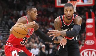 Portland Trail Blazers' Damian Lillard, right, passes past Chicago Bulls' Kris Dunn during the first half of an NBA basketball game Monday, Nov. 25, 2019, in Chicago. (AP Photo/Charles Rex Arbogast)