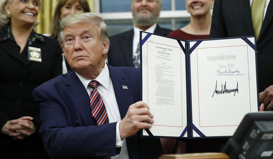 President Donald Trump displays the Preventing Animal Cruelty and Torture Act after signing it during a ceremony in the Oval Office of the White House, Monday, Nov. 25, 2019, in Washington. (AP Photo/Patrick Semansky)