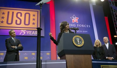 First lady Michelle Obama, center, points back to her husband President Barack Obama, left, as she speaks at the podium to help kick off the 5th anniversary of Joining Forces and the 75th anniversary of the USO, during ceremonies at Andrews Air Force Base, Md., Thursday, May 5, 2016. Also on stage are Vice President Joe Biden and his wife Jill Biden. (AP Photo/Pablo Martinez Monsivais)