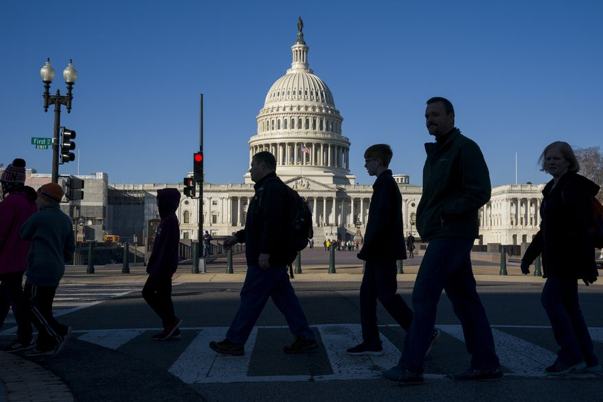 In this Nov. 26, 2019, file photo, people are showing walking in front of the East Front of the U.S. Capitol building. (AP Photo/J. Scott Applewhite)