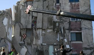 Rescuers search at a damaged building after a magnitude 6.4 earthquake in Thumane, western Albania, Tuesday, Nov. 26, 2019. Rescue crews used excavators to search for survivors trapped in toppled apartment buildings after a powerful pre-dawn earthquake in Albania killed at least six people and injured more than 300. (AP Photo/Visar Kryeziu)
