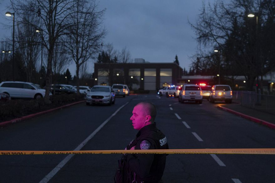 A Clark County Sheriff's deputy watches traffic pass by Sarah J. Anderson Elementary School in Vancouver, Wash., following a shooting on the school's campus on Tuesday, Nov. 26, 2019. (Nathan Howard/The Columbian via AP)