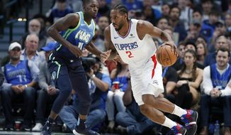 Dallas Mavericks forward Dorian Finney-Smith (10) defends as Los Angeles Clippers forward Kawhi Leonard (2) works for a shot opportunity in the first half of an NBA basketball game in Dallas, Tuesday, Nov. 26, 2019. (AP Photo/Tony Gutierrez)