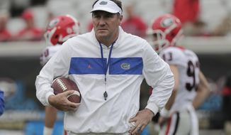 In this Nov. 2, 2019 file photo Florida head coach Dan Mullen walks on the field before an NCAA college football game against Georgia in Jacksonville, Fla. Mullen is unbeaten against Florida State. The eighth-ranked Gators (9-2) have dropped four straight at home to their biggest in-state rival, a decade-old skid they hope to end Saturday, Nov. 30, 2019 in the Swamp. (AP Photo/John Raoux)