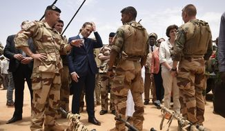 In this May 19, 2017, file photo, French President Emmanuel Macron, center left, visits soldiers of Operation Barkhane, France's largest overseas military operation, in Gao, Northern Mali. Macron said Tuesday Nov. 26, 2019, that a midair collision between two helicopters has killed 13 French soldiers fighting against Islamic extremists in Mali. (Christophe Petit Tesson, Pool via AP)