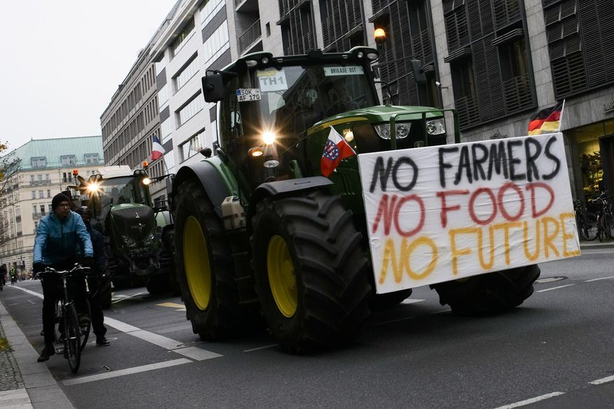 Farmers with tractors arrive for a protest at the government district in Berlin, Germany, Tuesday, Nov. 26, 2019. Some thousands farmers expected in the German capital for a protest against the German and European agriculture policy.(AP Photo/Markus Schreiber)