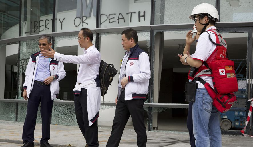 Prof. Alex Wai, second from left, a vice president with the Hong Kong Polytechnic University prepares to lead a team to look for holed up protesters on the university campus in Hong Kong, Tuesday, Nov. 26, 2019. Hong Kong's embattled leader Carrie Lam refused to offer any concessions to anti-government protesters despite a local election trouncing, saying Tuesday that she will instead accelerate dialogue and identify ways to address societal grievances. (AP Photo/Ng Han Guan)