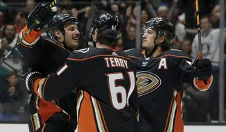 Anaheim Ducks center Ryan Getzlaf, left, celebrates his goal with center Troy Terry, center, and right wing Rickard Rakell, right, of Sweden, during the second period of an NHL hockey game against the New York Islanders in Anaheim, Calif., Monday, Nov. 25, 2019. (AP Photo/Alex Gallardo)