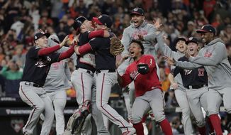 In this Oct. 30, 2019, file photo, Washington Nationals' Yan Gomes and Daniel Hudson celebrate after Game 7 of the baseball World Series against the Houston Astros, in Houston. (AP Photo/David J. Phillip, File) **FILE**