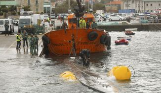 Spanish civil guard tow a sunken submarine believed to be carrying tons of cocaine in Aldan harbour, northwest Spain, Tuesday, Nov. 26, 2019. Spanish authorities said it was the first time a submarine had been found to be used in drug trafficking in the country. (Marta Vazquez Rodriguez/Europa Press via AP)