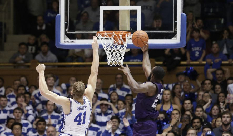 Stephen F. Austin forward Nathan Bain (23) drives for a game winning basket over Duke forward Jack White (41) during overtime in an NCAA college basketball game in Durham, N.C., Tuesday, Nov. 26, 2019. Stephen F. Austin won 85-83. (AP Photo/Gerry Broome) **FILE**