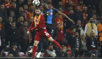 Galatasaray's Omer Bayram, left, jumps for the ball with Brugge's Amadou Sagna during the Champions League group A soccer match between Galatasaray and Club Brugge in Istanbul, Tuesday, Nov. 26, 2019. (AP Photo/Lefteris Pitarakis)