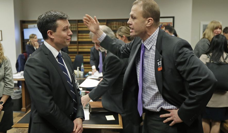 Tim Eyman, right, a career anti-tax initiative promoter, argues with Noah Purcell, left, Solicitor General of the State of Washington, following a King County Superior Court hearing, Tuesday, Nov. 26, 2019, in Seattle. Lawyers for cities and counties across Washington state were in court to ask King County Judge Marshall Ferguson to block Eyman's $30 I-976 car tab measure from taking effect, saying it was misleading and violates Washington's Constitution. (AP Photo/Ted S. Warren)