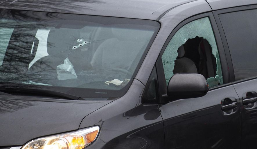 Bullet holes are seen here in the windows of a van in the parking lot of Sarah J. Anderson Elementary School in Vancouver, Wash., following a shooting on Tuesday, Nov. 26, 2019. Authorities say a man shot several people in a Vancouver, Wash., elementary school parking lot and then shot himself after a police chase. (Nathan Howard/The Columbian via AP)
