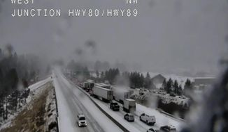 """In this still image taken from a Caltrans remote video traffic camera, traffic is stopped along Interstate 80 because of multiple spinouts, Tuesday, Nov. 26, 2019, in Truckee, Calif. Northern California and southern Oregon residents are bracing for a """"bomb cyclone"""" weather phenomenon that's expected at one of the busiest travel times of the year. The National Weather Service says the storm expected Tuesday into Wednesday could be like nothing experienced in the area for 20 years. (Caltrans via AP)"""