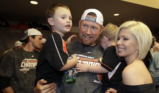 San Francisco Giants' Aubrey Huff celebrates with his sons Jayce, left, and Jagger, and his wife Barbara after the Giants defeated the San Diego Padres to win the National League West Division title after a baseball game, Saturday, Sept 22, 2012, in San Francisco. The Giants won 8-4. (AP Photo/Ben Margot, Pool)