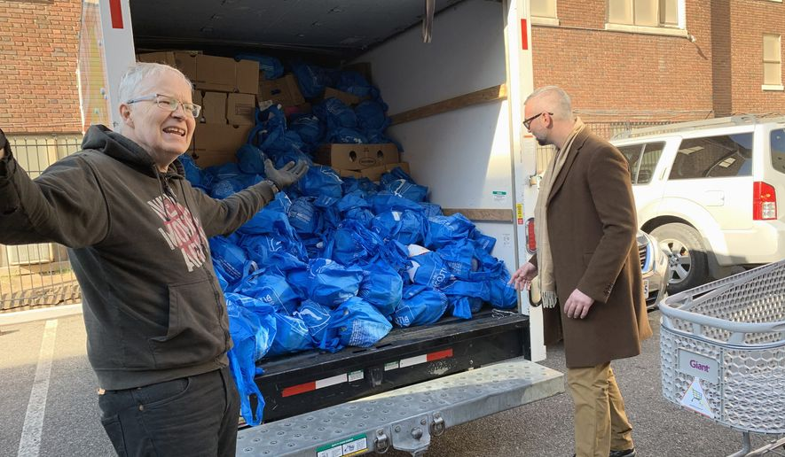 Mark Andersen (left) prepares to deliver a truckload of Thanksgiving turkeys to elderly residents in Northwest on Tuesday, Nov. 26, 2018. Mr. Andersen is the co-director of We Are Family, a nonprofit volunteer group. Photo by Sophie Kaplan / The Washington Times