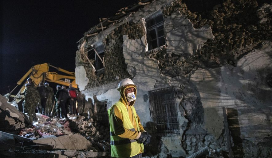 Rescuers search a collapsed building after a magnitude 6.4 earthquake in Thumane, western Albania, Tuesday, Nov. 26, 2019. Rescue crews with excavators searched for survivors trapped in toppled apartment buildings and hotels Tuesday as the death toll from a powerful pre-dawn earthquake in Albania climbed to 21, with more than 600 people injured. (AP Photo/Petros Giannakouris)