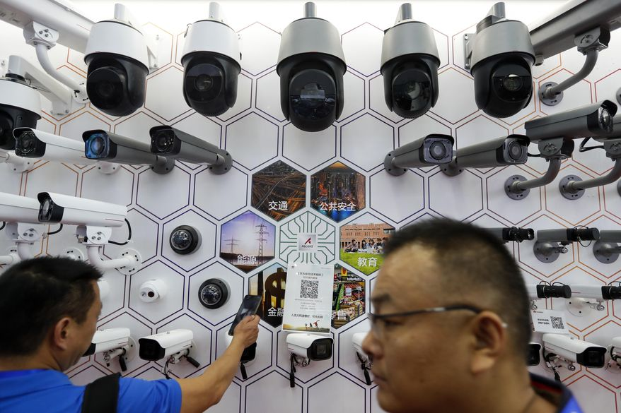 In this Tuesday, Oct. 29, 2019, photo, visitors look at the surveillance cameras and services provided by China's telecoms equipment giant Huawei on display at the China Public Security Expo in Shenzhen, China's Guangdong province. The U.S. Department of Commerce has proposed requiring case-by-case approvals of all purchases of telecommunications equipment in a move likely to hit major Chinese suppliers like Huawei. (AP Photo/Andy Wong)