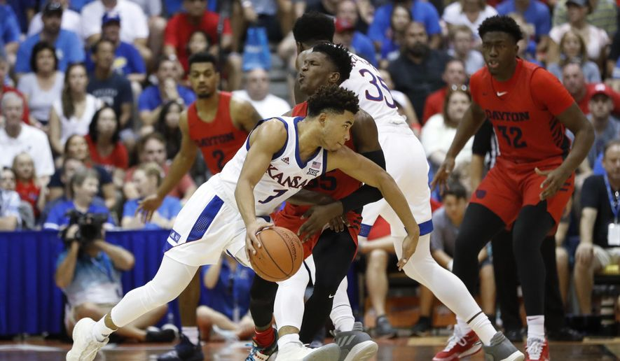 Kansas guard Devon Dotson (1) collides Dayton guard Dwayne Cohill during the first half of an NCAA college basketball game Wednesday, Nov. 27, 2019, in Lahaina, Hawaii. (AP Photo/Marco Garcia)