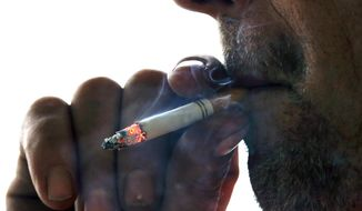 FILE - In this Nov. 6, 2014, file photo, a man smokes a cigarette on Main Street in Westminster, Mass. Massachusetts Gov. Charlie Baker is expected to sign a law on Wednesday, Nov. 27, 2019, banning sales of flavored tobacco and vaping products, including menthol cigarettes. (AP Photo/Elise Amendola), File