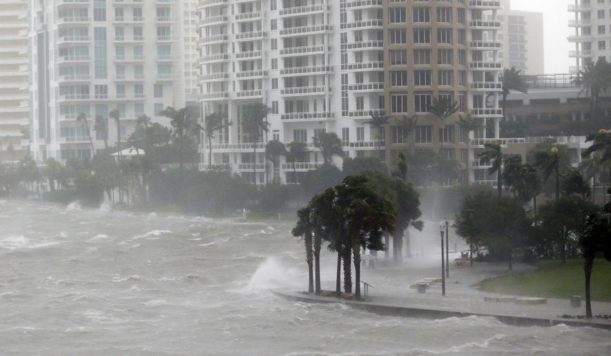 FILE - In this Sept. 10, 2017 file photo, waves crash over a seawall at the mouth of the Miami River from Biscayne Bay, Fla., as Hurricane Irma passes by in Miami. In his first 10 months in office, Florida Gov. Ron DeSantis has appointed a science officer, established a czar on climate change and pushed action against red tide and algae blooms. (AP Photo/Wilfredo Lee)