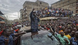 FILE - In this Sunday, Aug. 13, 2017 file photo, Kenyan opposition leader Raila Odinga gestures to thousands of supporters gathered in the Mathare slum of Nairobi, Kenya. Kenya's president and top opposition leader launched a report Wednesday, Nov. 27, 2019 that they call a road map for unifying the country and ending deadly violence around elections. (AP Photo/Ben Curtis, File)