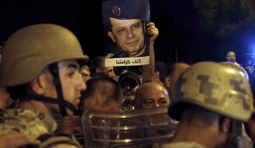 """A supporter of Lebanese President Michel Aoun holds up his picture with Arabic that read """"Because you are our dignity,"""" as Lebanese republican guards stand guard during a protest near the presidential palace in the Beirut suburb of Baabda, Lebanon, Tuesday, Nov. 26, 2019. Dozens of people are marching to show their support for Aoun and his proposed political reforms that come after more than five weeks of widespread anti-government demonstrations. (AP Photo/Bilal Hussein)"""