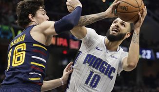 Orlando Magic's Evan Fournier (10) drives to the basket against Cleveland Cavaliers' Cedi Osman (16) in the second half of an NBA basketball game, Wednesday, Nov. 27, 2019, in Cleveland. Orlando won 116-104. (AP Photo/Tony Dejak)