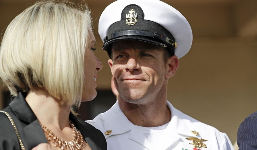 In this July 2, 2019, file photo, Navy Special Operations Chief Edward Gallagher, right, walks with his wife, Andrea Gallagher as they leave a military court on Naval Base San Diego, in San Diego. (AP Photo/Gregory Bull, File)
