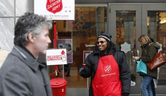 In this Friday, Nov. 15, 2019, photo, bell ringer Carolyn Harper encourages people to donate to the Salvation Army's annual holiday red kettle campaign on Chicago's Magnificent Mile. Cashless shoppers have a new option to give to the Army's red kettle campaign this year using their smartphone. Leaders hope adding Apple and Google payment options will boost fundraising to the campaign, which makes up 10% of The Salvation Army's annual budget. Those donations fund programs providing housing, food and other support to people in poverty. (AP Photo/Charles Rex Arbogast)