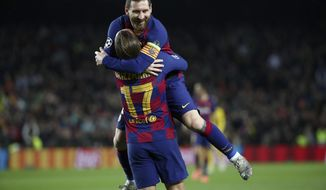 Barcelona's Antoine Griezmann celebrates with teammate Lionel Messi, top, after scoring his side's third goal during a Champions League group F soccer match between Barcelona and Dortmund at the Camp Nou stadium in Barcelona, Spain, Wednesday, Nov. 27, 2019. (AP Photo/Emilio Morenatti)