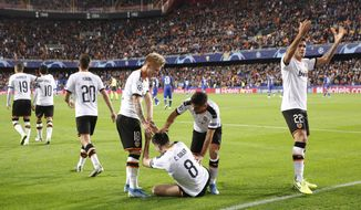 Valencia's players celebrate after scoring the opening goal during the Champions League group H soccer match between Valencia and Chelsea at the Mestalla stadium in Valencia, Spain, Wednesday, Nov. 27, 2019. (AP Photo/Alberto Saiz)