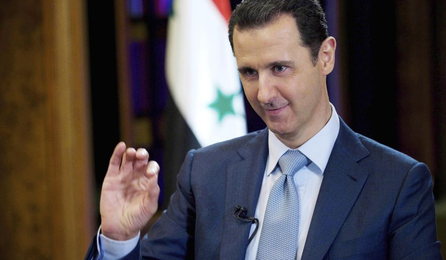 FILE - In this Feb. 10, 2015, file photo released by the Syrian official news agency SANA, Syrian President Bashar Assad gestures during an interview in Damascus, Syria. Assad says members of the Islamic State group held in the country will stand trial in local courts specialized in cases of terrorism. Assad made his comments in an interview with Paris Match when asked about a deal with a Kurdish-led force that would eventually bring their areas under government control. (SANA via AP, File)