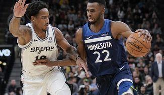 Minnesota Timberwolves' Andrew Wiggins (22) drives against San Antonio Spurs' DeMar DeRozan during the first half of an NBA basketball game, Wednesday, Nov. 27, 2019, in San Antonio. (AP Photo/Darren Abate)
