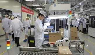 FILE - In this March 6, 2019, file photo, staff members work on a mobile phone production line during a media tour in Huawei factory in Dongguan, China's Guangdong province. The Department of Commerce has proposed requiring case-by-case approvals of all transactions related to telecommunications in a move seen likely to affect Chinese suppliers like Huawei. (AP Photo/Kin Cheung, File)