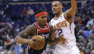 Washington Wizards guard Bradley Beal (3) drives on Phoenix Suns forward Elie Okobo in the first half during an NBA basketball game, Wednesday, Nov. 27, 2019, in Phoenix. (AP Photo/Rick Scuteri) ** FILE **