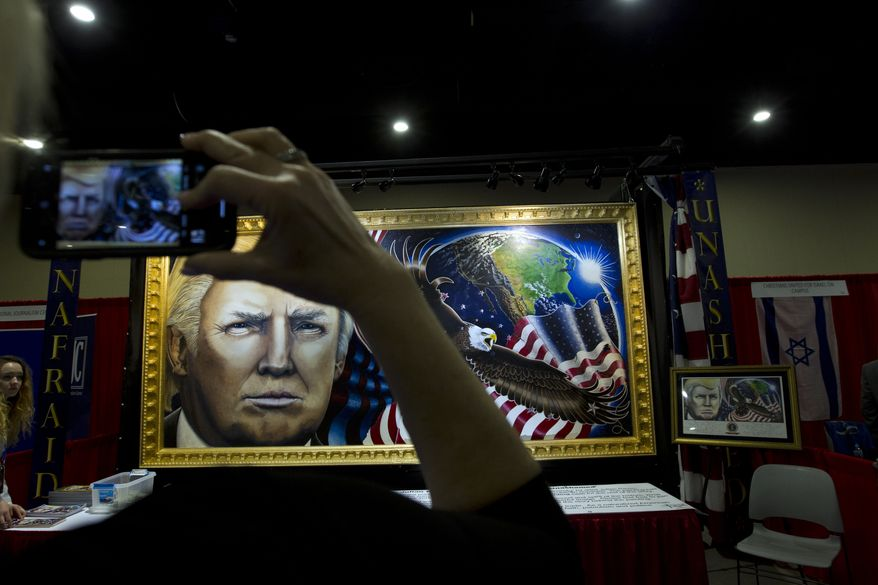 A attendee take a picture of a painting with the face of President Donald Trump during the Conservative Political Action Conference, CPAC 2019, in Oxon Hill, Md., Friday, March 1, 2019. (AP Photo/Jose Luis Magana)